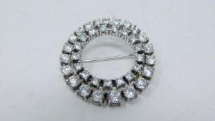 A white stone circular white metal brooch set with thirty eight round white paste stones in four