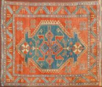 A Kazak rug with central medallion on azure ground within a pale burgundy field and stylised