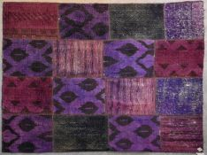 A flat weave rug with patchwork design in various magenta hues. L.237x175cm