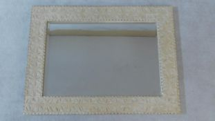 A vintage wall mirror in limed and carved frame fitted with bevelled plate. 122x92cm
