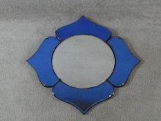An Art Deco circular wall mirror set within a quatrefoil blue glass frame. H.55xW.55cm