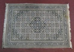 An Indian woollen rug with allover repeating floral motifs on ivory field within naturalistic