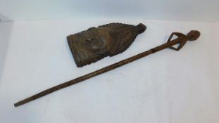An African carved wooden tribal mask from Sierra Leone and a tribal wooden staff with a carved