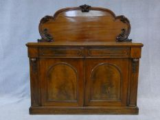 A Victorian flame mahogany chiffonier with shaped and carved back above pair of frieze drawers above