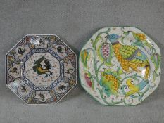 Two large octagonal hand painted ceramic Majolica chargers. One with a stylised bird among