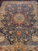 A Persian style carpet with central floral medallion and allover bird, urn and scrolling foliate