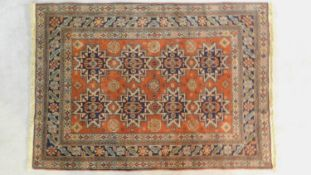 A Shirvan rug with repeating geometric medallions on a burgundy field within floral midnight multi