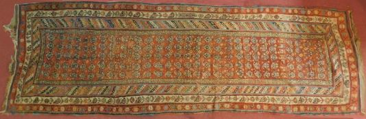 A Russian Kazakh runner with allover repeating stylised floral motifs on rouge ground contained