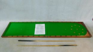 A vintage folding table top bagatelle table in mahogany case lined with green baize, with two cues