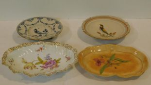Four antique hand painted plates. Inlcluding a ceramic plate with a painted Spiderwort, two