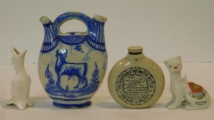 A collection of antique ceramic items. Including a blue and white Delft twin spout jug with cow