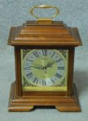 A Georgian style mahogany cased mantel clock with brass carrying handle on stepped bracket feet. H.