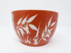 A small Chinese rice bowl with bamboo and calligraphy decoration on a deep red ground, character