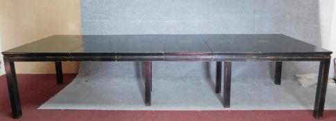A Chinese ebonised and lacquered extending dining table with four extra leaves on square section