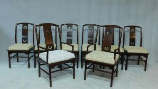 A set of eight Chinese hardwood dining chairs with carved splat backs and fitted squab cushions on