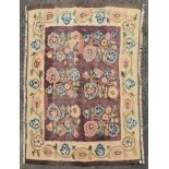 An antique Bessarabian Kilim rug with repeating highly stylised flowerhead design on a chocolate