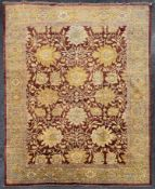 A Ziegler style carpet with repeating meandering vine and palmette design on a deep burgundy