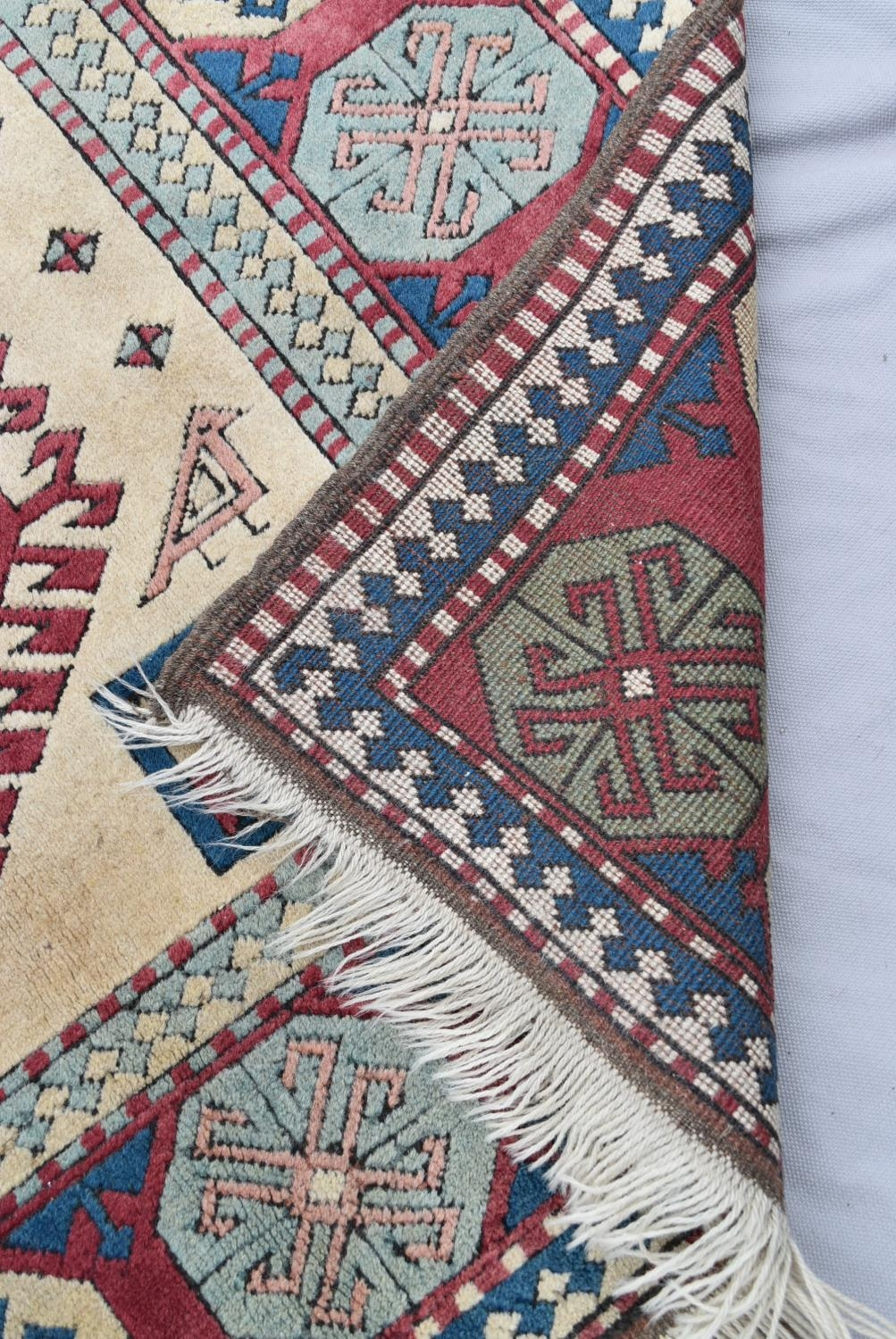 A Turkish Kazak carpet with triple stylised gul medallions on a fawn ground within stylised - Image 5 of 5