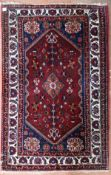 A Persian Abadeh rug with floral pole medallion on a madder field within spandrels with gul motifs