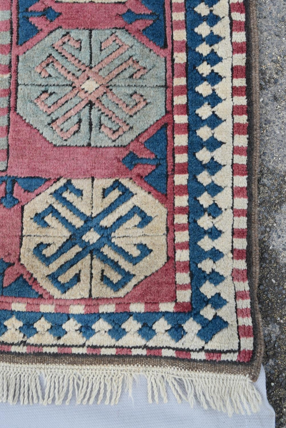 A Turkish Kazak carpet with triple stylised gul medallions on a fawn ground within stylised - Image 3 of 5