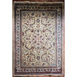 An old Persian Tabriz carpet with a repeating scrolling foliate design on a cream field within