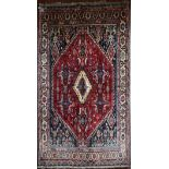 A Persian Kashkai rug with central lozenge medallion on madder ground contained within floral