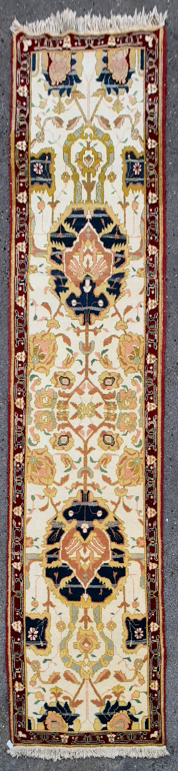 An Agra design runner with double palmette pole medallion on a fawn field within stylised foliate