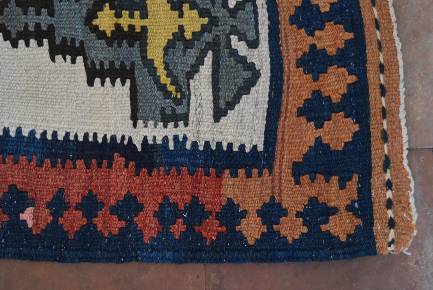 A Persian Kilim with repeating lozenge medallion on umber ground contained by plain spandrels and - Image 3 of 4