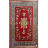 A Persian Qum rug with central medallion decorated with lotus flowers on a burgundy field with
