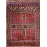 An Afghan rug with geometric design across the madder field within stylised floral borders. L.