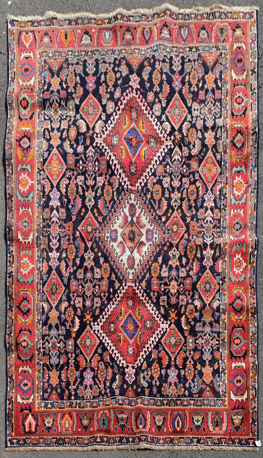 A Persian Kashkai rug with triple hooked medallions on a midnight ground within a stylised multi