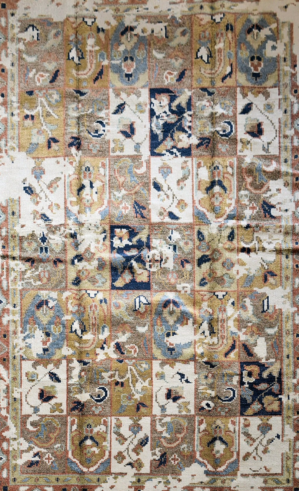 A Bakhtiar Design carpet with floral panels across the field enclosed by stylised geometric borders.