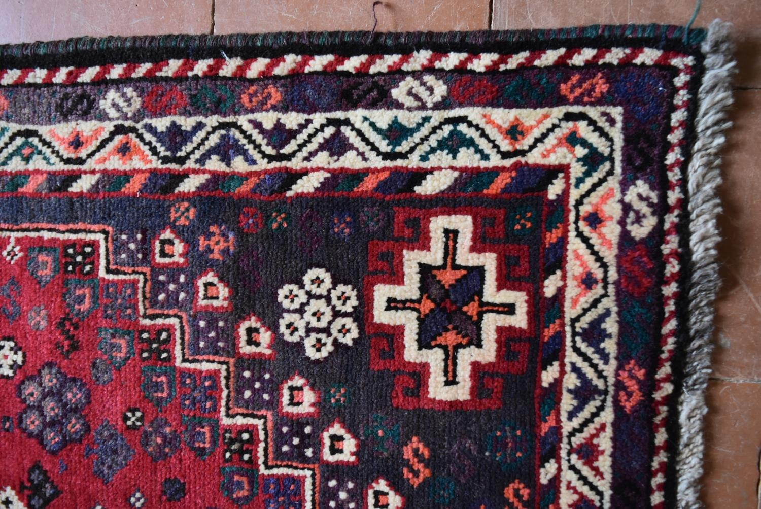 A Persian Shiraz rug with triple pole medallions on a madder ground contained by stylised floral - Image 3 of 4
