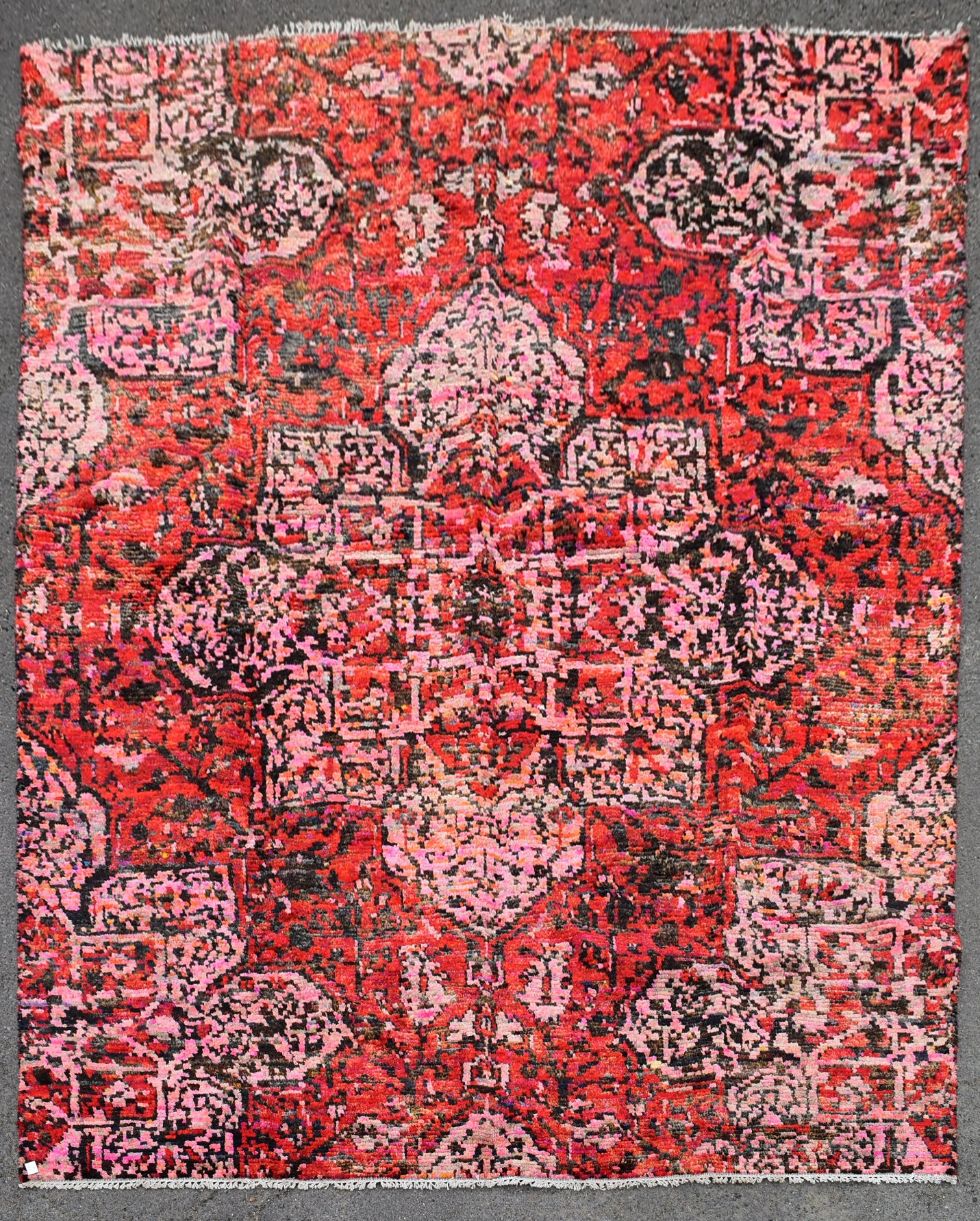 A contemporary design Persian style woollen carpet with large central medallion on a rouge field