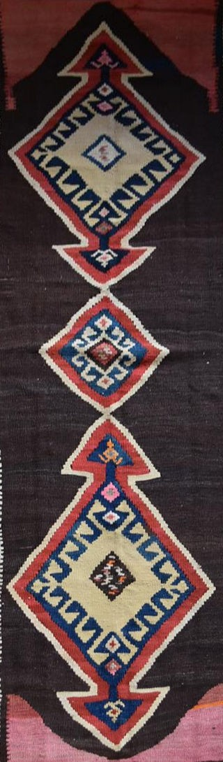 A Persian Kilim with repeating lozenge medallion on umber ground contained by plain spandrels and - Image 2 of 4