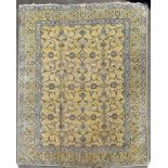 A Persian Kashan carpet with palmettes and scrolling foliate design on a biscuit ground contained by