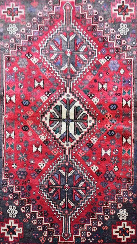 A Persian Shiraz rug with triple pole medallions on a madder ground contained by stylised floral - Image 2 of 4