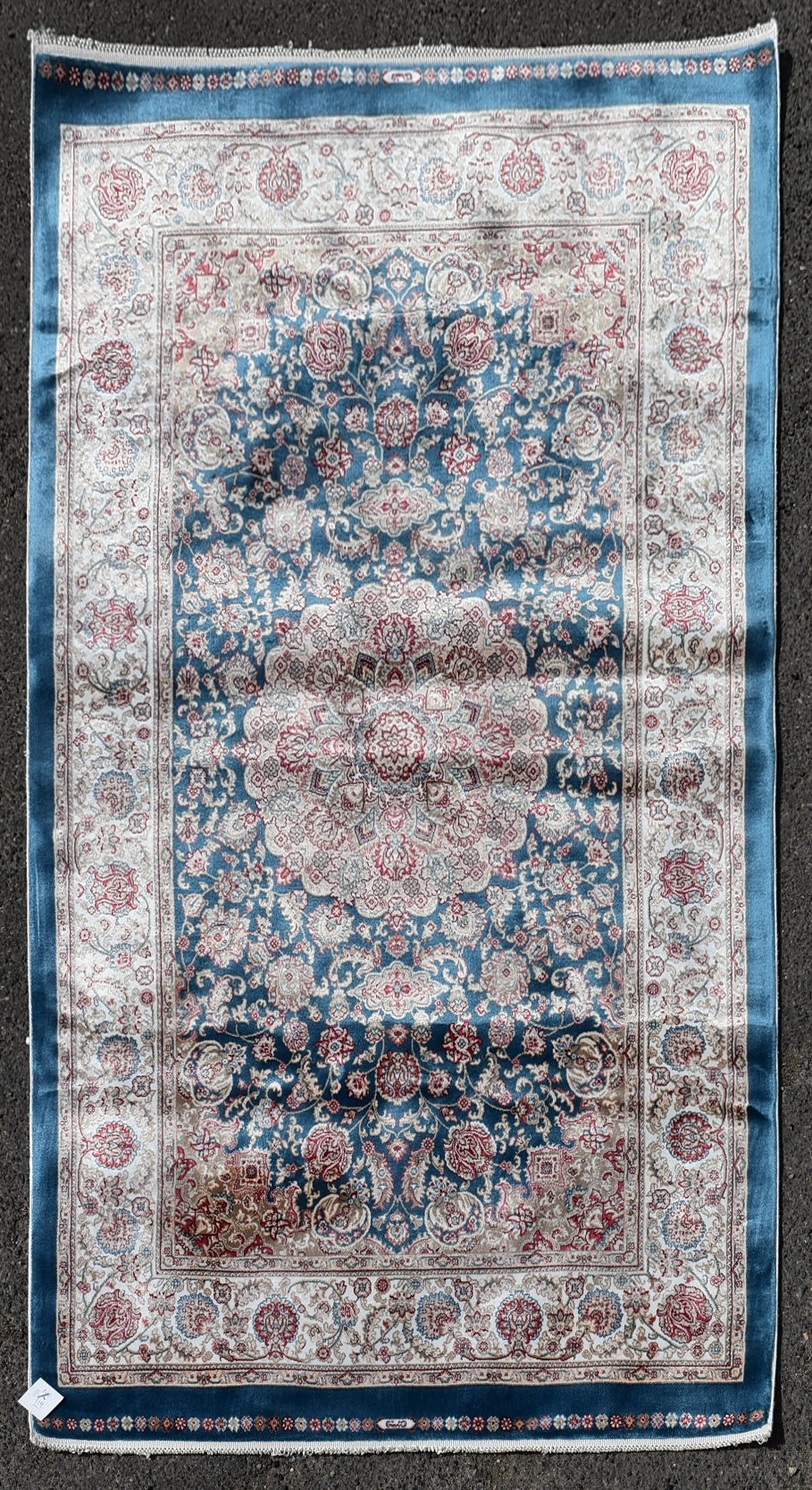 A Persian style rug with central floral medallion on a sapphire ground contained by naturalistic