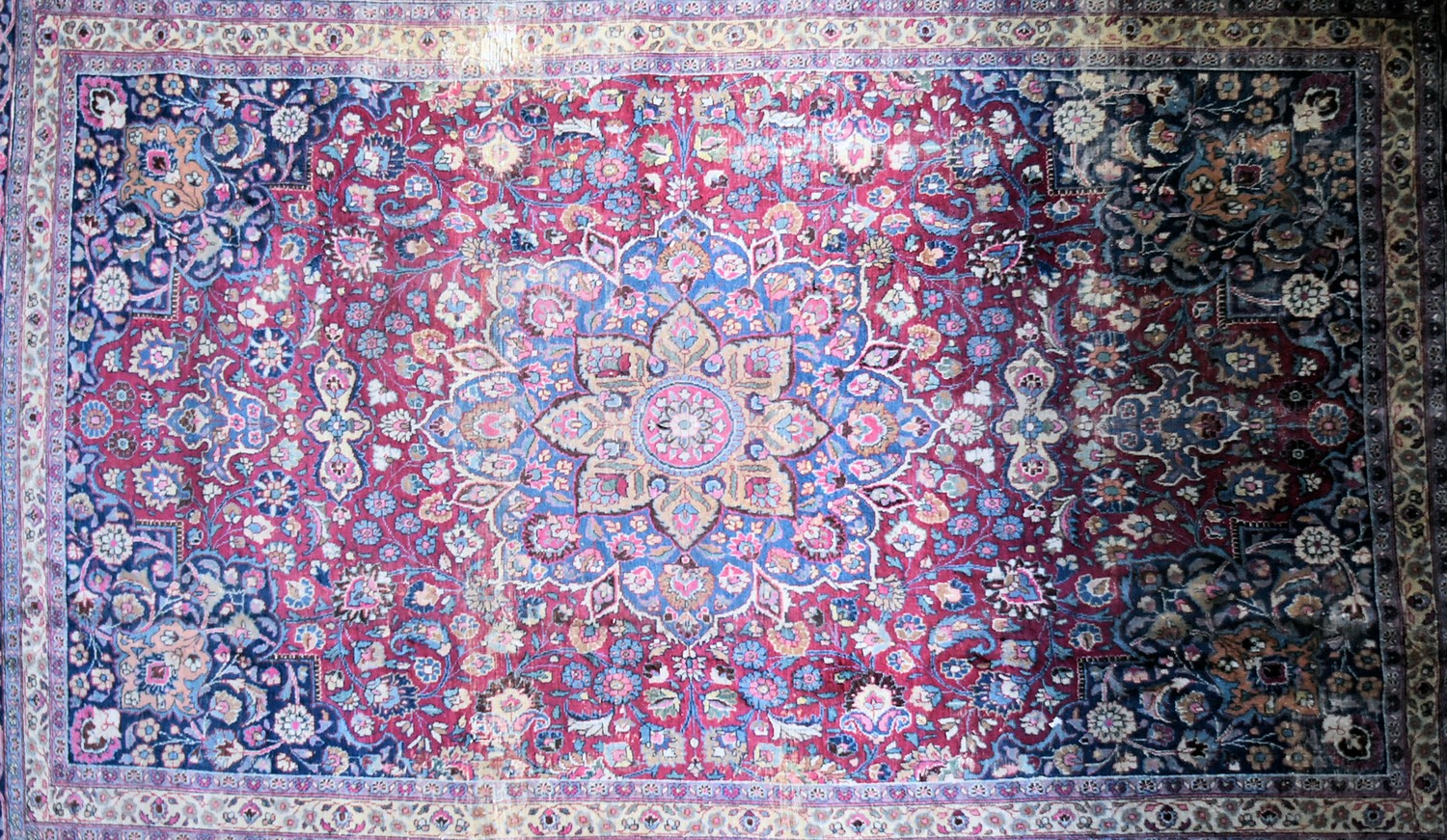 A Persian Mashad carpet with double central floral medallions on madder field within sapphire floral - Image 2 of 4