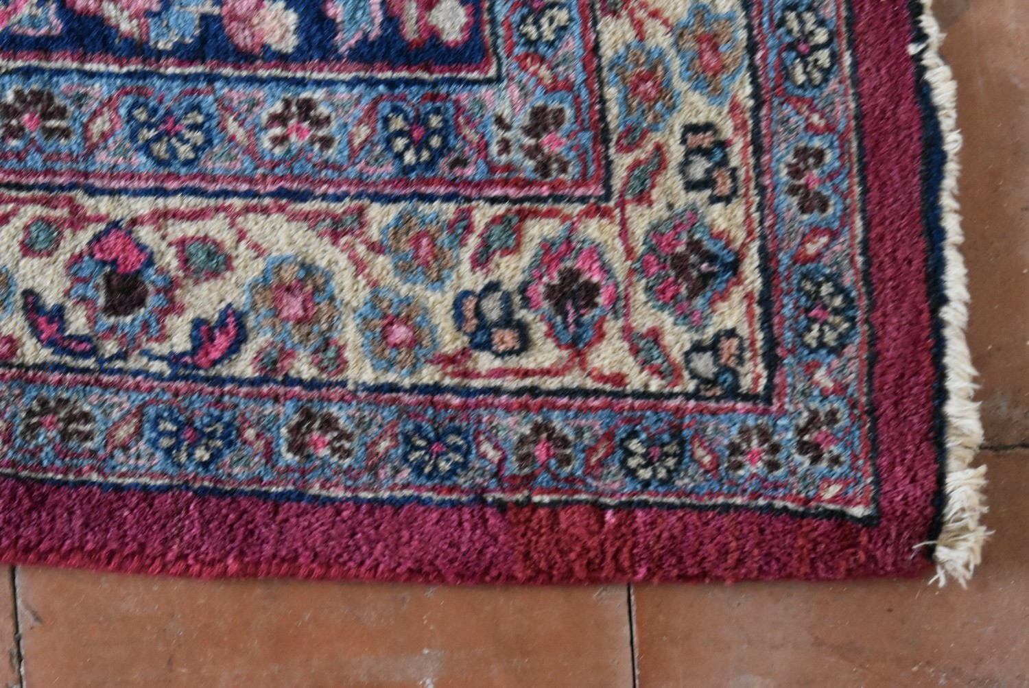 A Persian Mashad carpet with double central floral medallions on madder field within sapphire floral - Image 3 of 4
