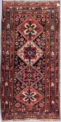 An antique Kazak rug with repeating central medallions and flowerhead and animal motifs contained
