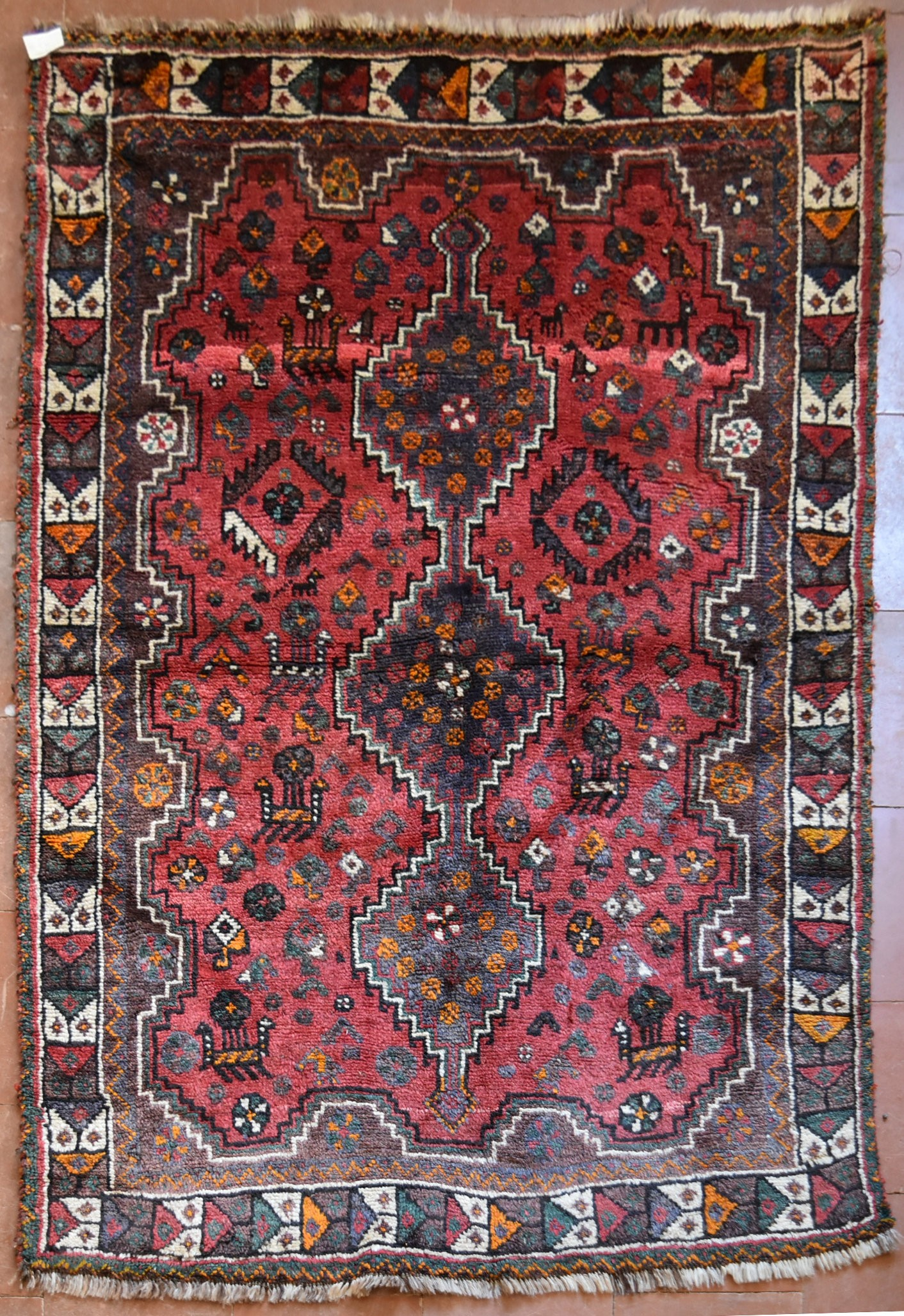 A Persian Shiraz rug with triple stepped pole medallion on burgundy field with stylised animal and
