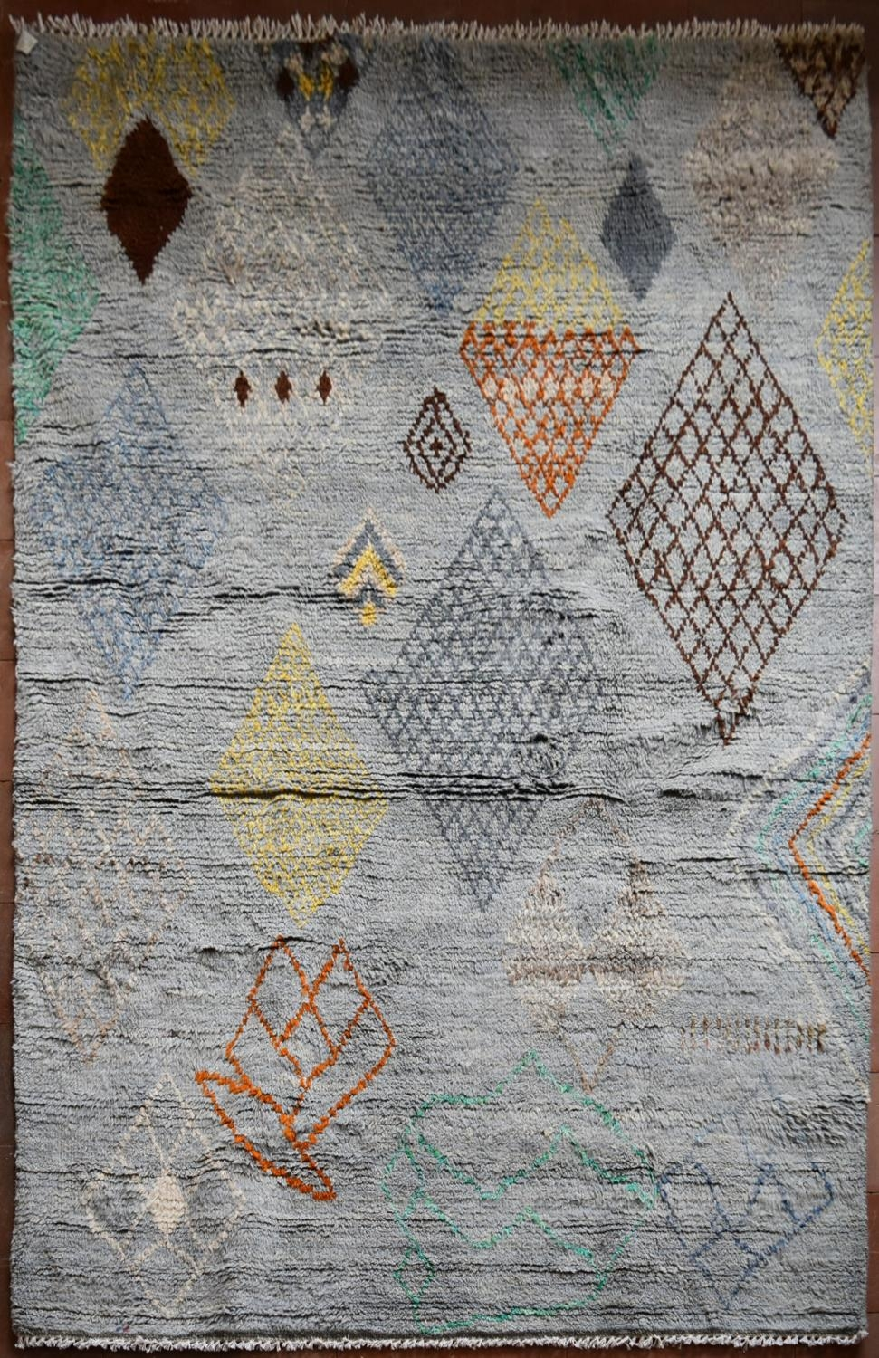 A Moroccan style rug with abstract diamond patterns across a powder blue ground. L.245xW.170cm