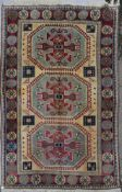 A Turkish Kazak carpet with triple stylised gul medallions on a fawn ground within stylised