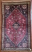 A Persian Kashkai rug with central stepped medallion and highly stylised motifs across a madder