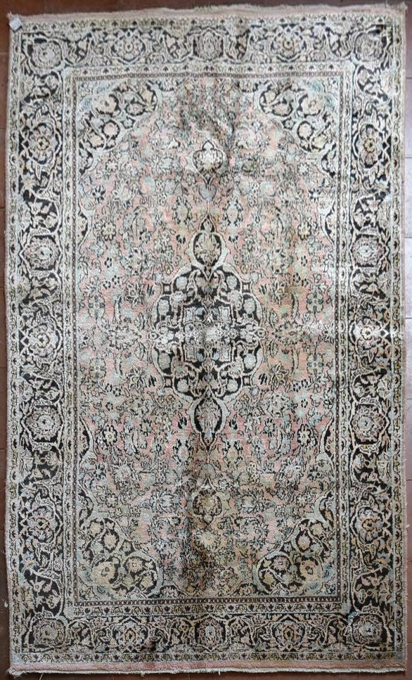 A silk Kashmir rug with central pendant medallion and scrolling floral design on a pale pink