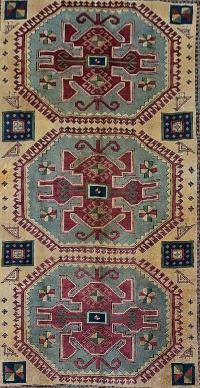 A Turkish Kazak carpet with triple stylised gul medallions on a fawn ground within stylised - Image 2 of 5
