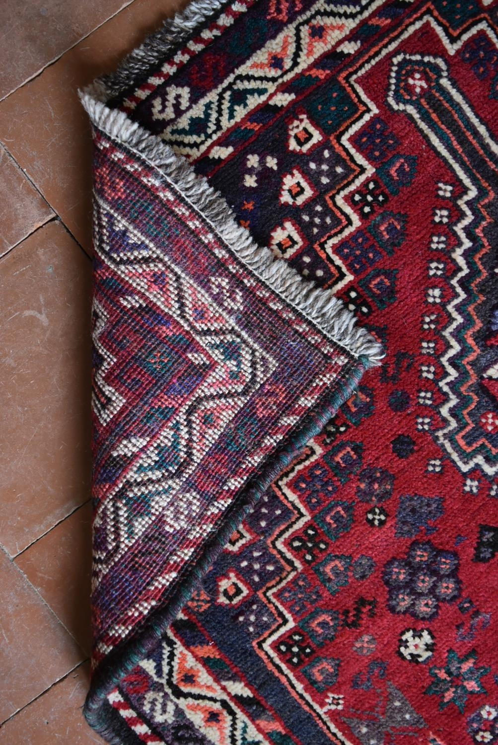 A Persian Shiraz rug with triple pole medallions on a madder ground contained by stylised floral - Image 4 of 4