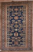 A Kazak rug with repeating stylised design across a midnight field within multiple borders. L.