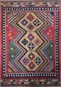 A Persian Kashkai Kilim with repeating diamond medallions on polychrome field contained by geometric